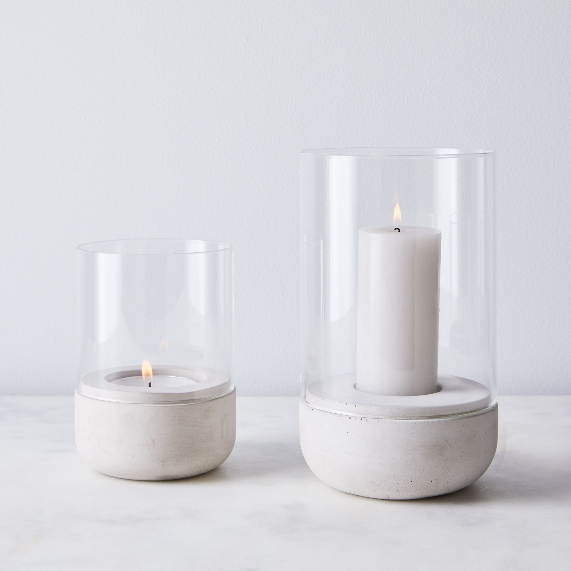 One tall and one short hurricane candle next to each-other.