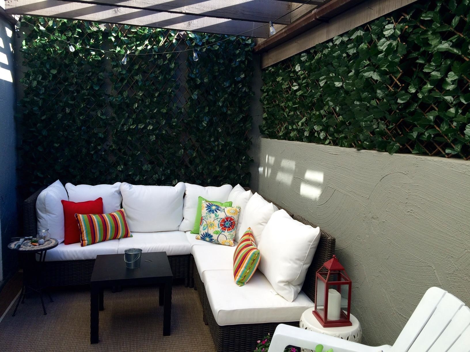 A small patio with the artificial greenery screen surrounding it on two sides.