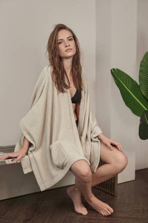 模特身着宽松,飘逸的长袍。 它有口袋,长袖子,而且落在臀部。