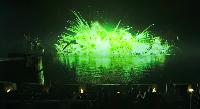 Game of Thrones still: green wildfire explodes over the water as shoulders watch on from the castle