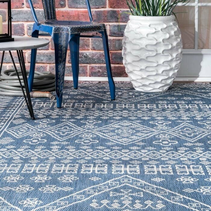 The blue and white patterned outdoor rug on a terrace.