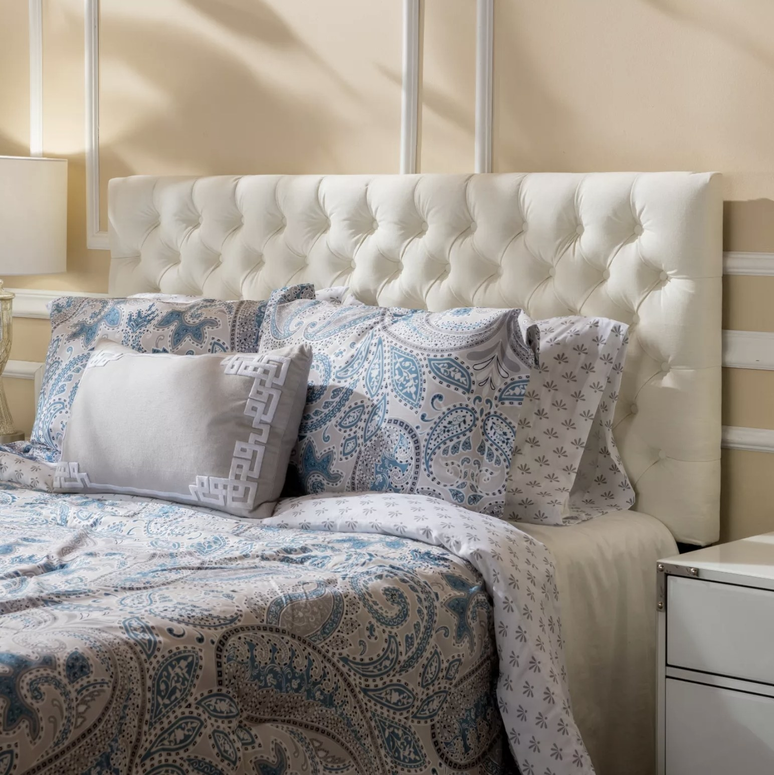 A white diamond button-tufted headboard behind a bed with paisley bedsheets and decorative pillows