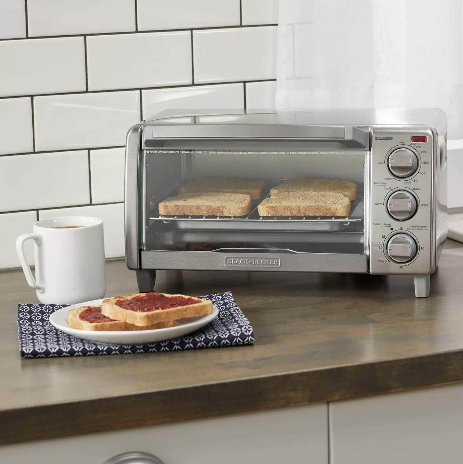 A stainless steel toaster oven in a kitchen with four slices of toast inside
