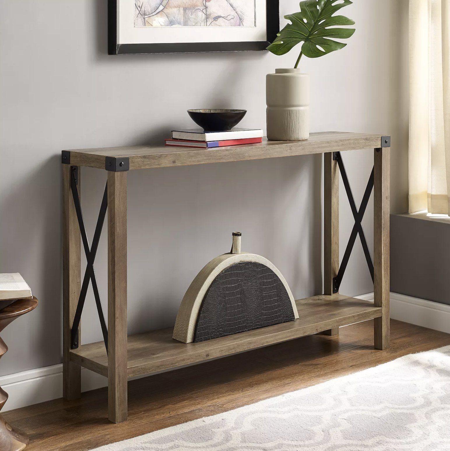 A light brown entryway table with metal accents sits in a living room