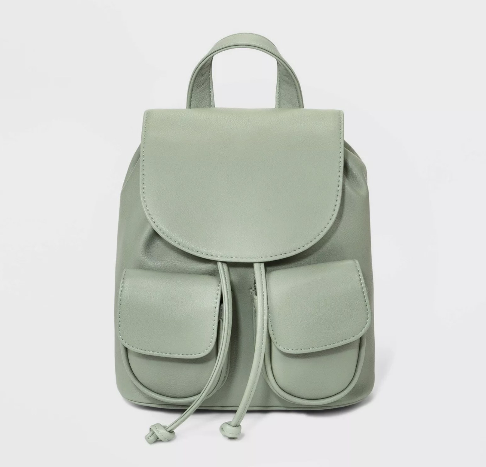 A mint green mini backpack with a flap opening and two pockets in the front