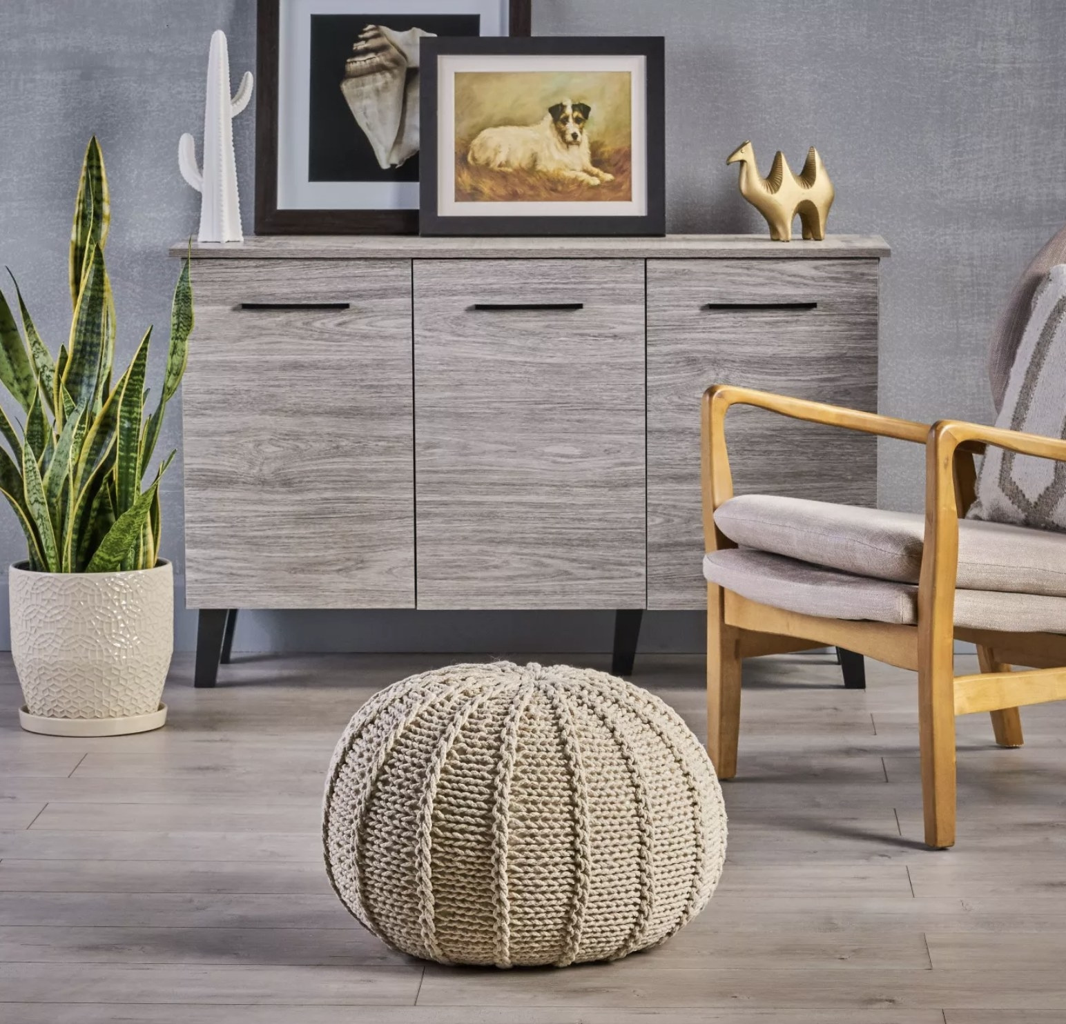 A white knitted cotton pouf with handcrafted details sits on the floor of a living room