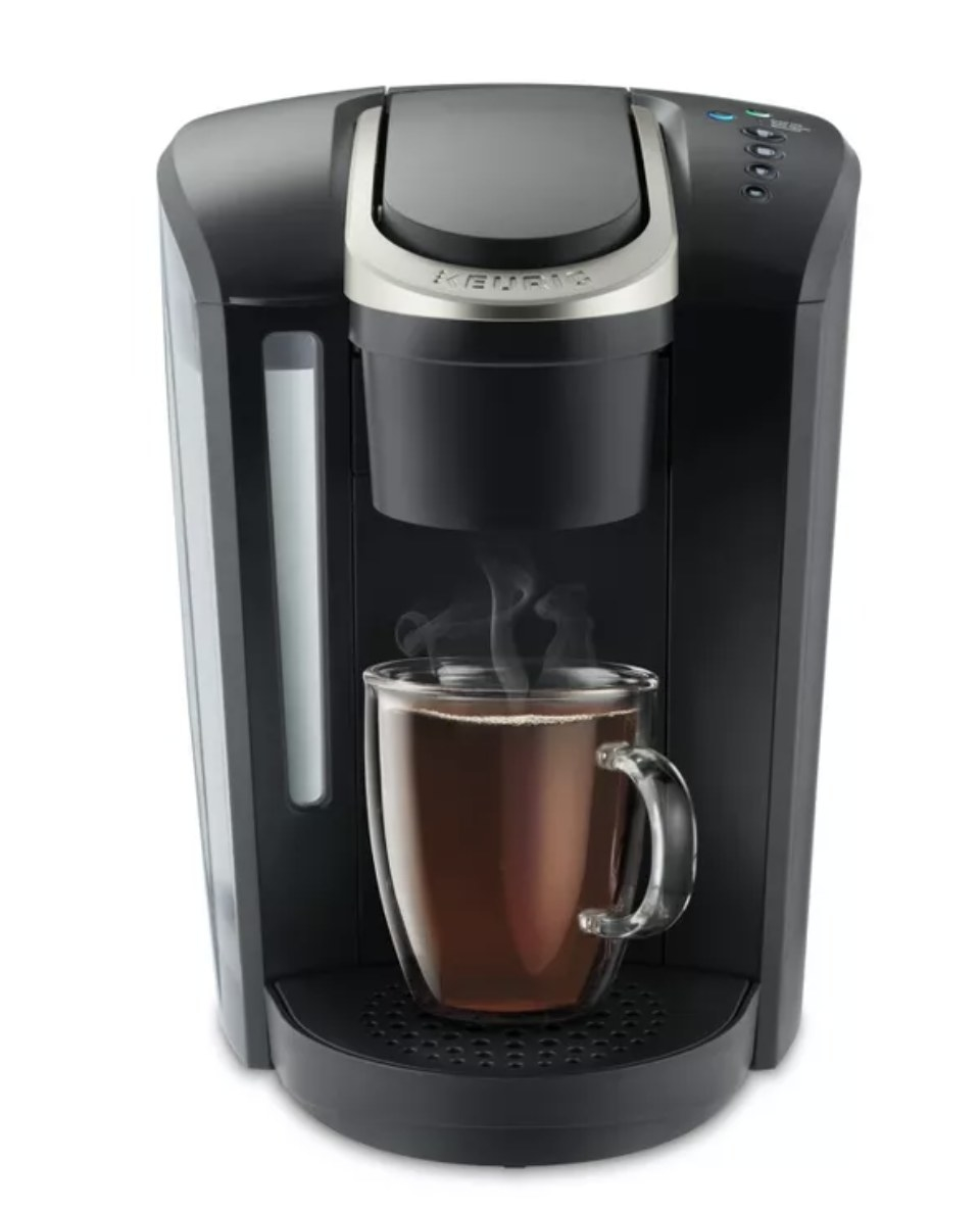 A black Keurig coffee maker with a glass mug full of hot coffee