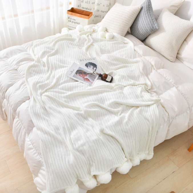 White pom-pom blanket on top of a large white comforter with magazines on top