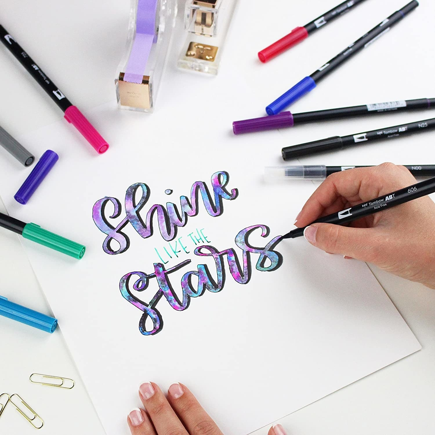 "A person writing ""shine like the stars"" with a brush pen"