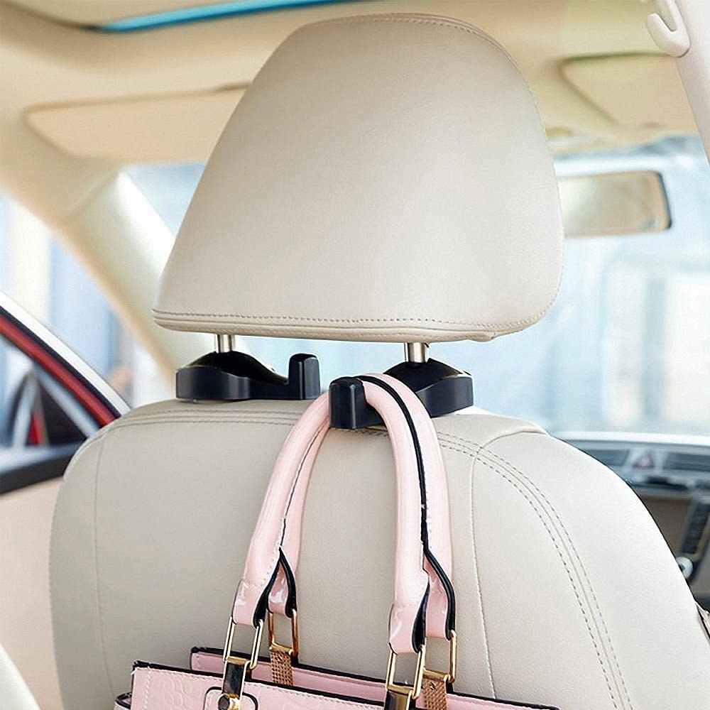 A purse hanging from a hook that's attached to a car head rest