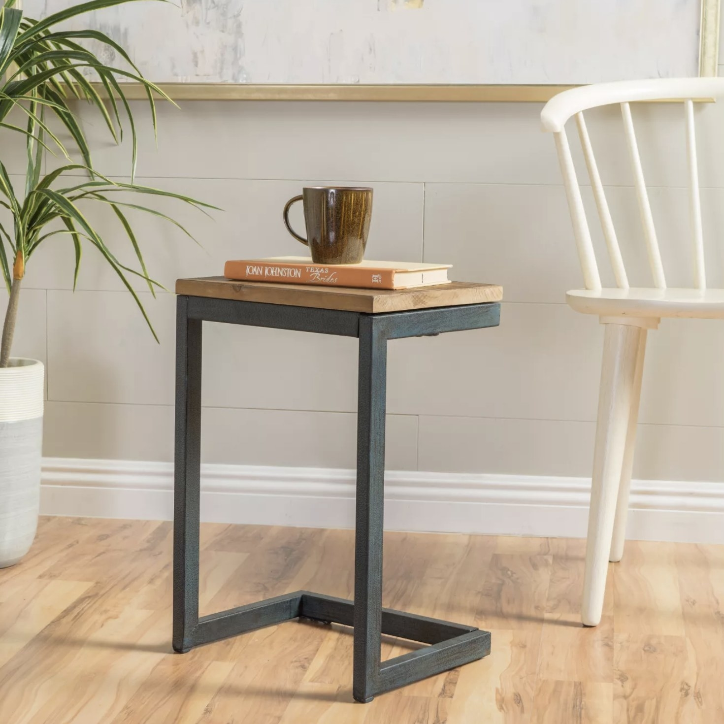 A c-table with an iron frame and wooden tabletop sits in a living space with a book and mug on top