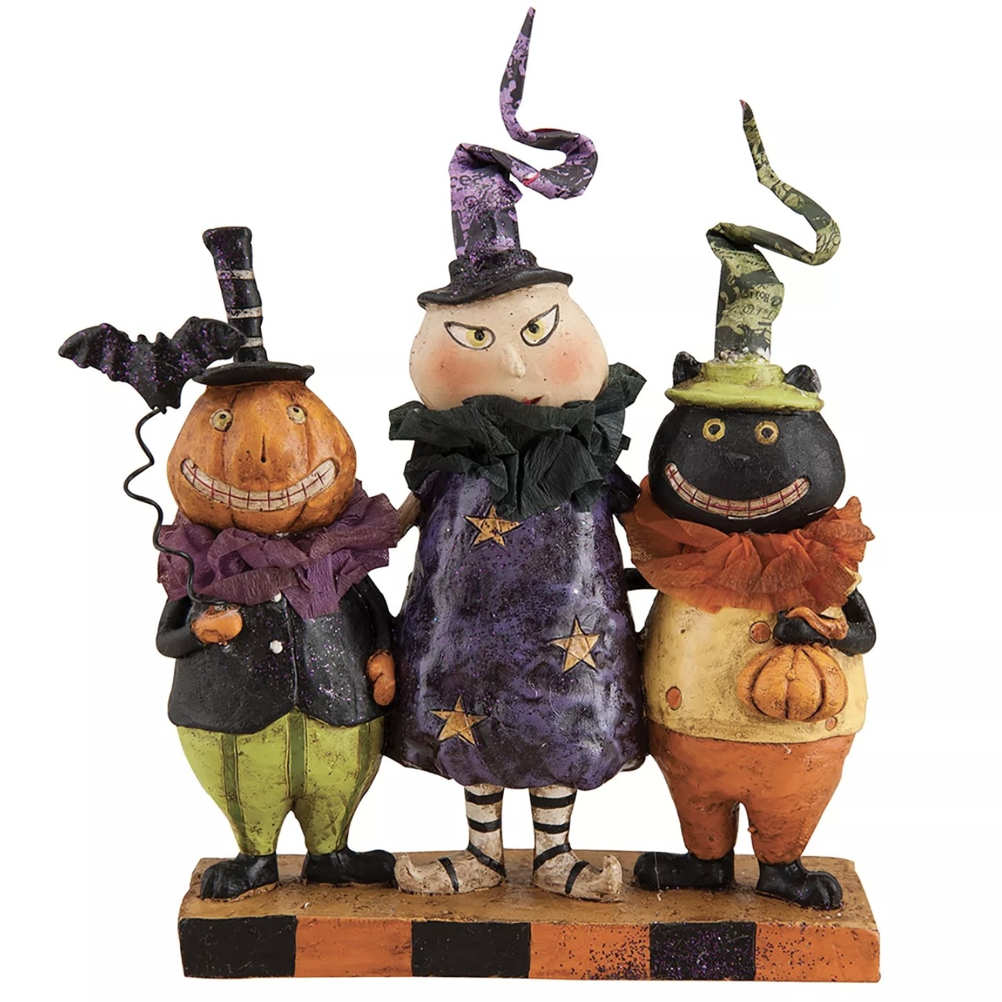 A ceramic figure of three trick or treaters with quirky hats and outfits