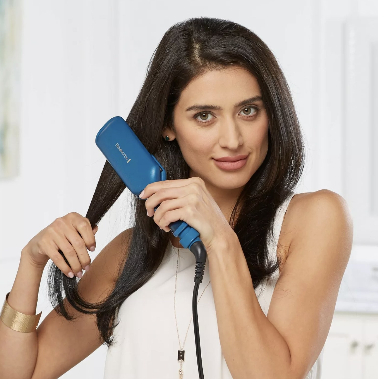 Model is using a blue 2-inch flat iron on their dark hair