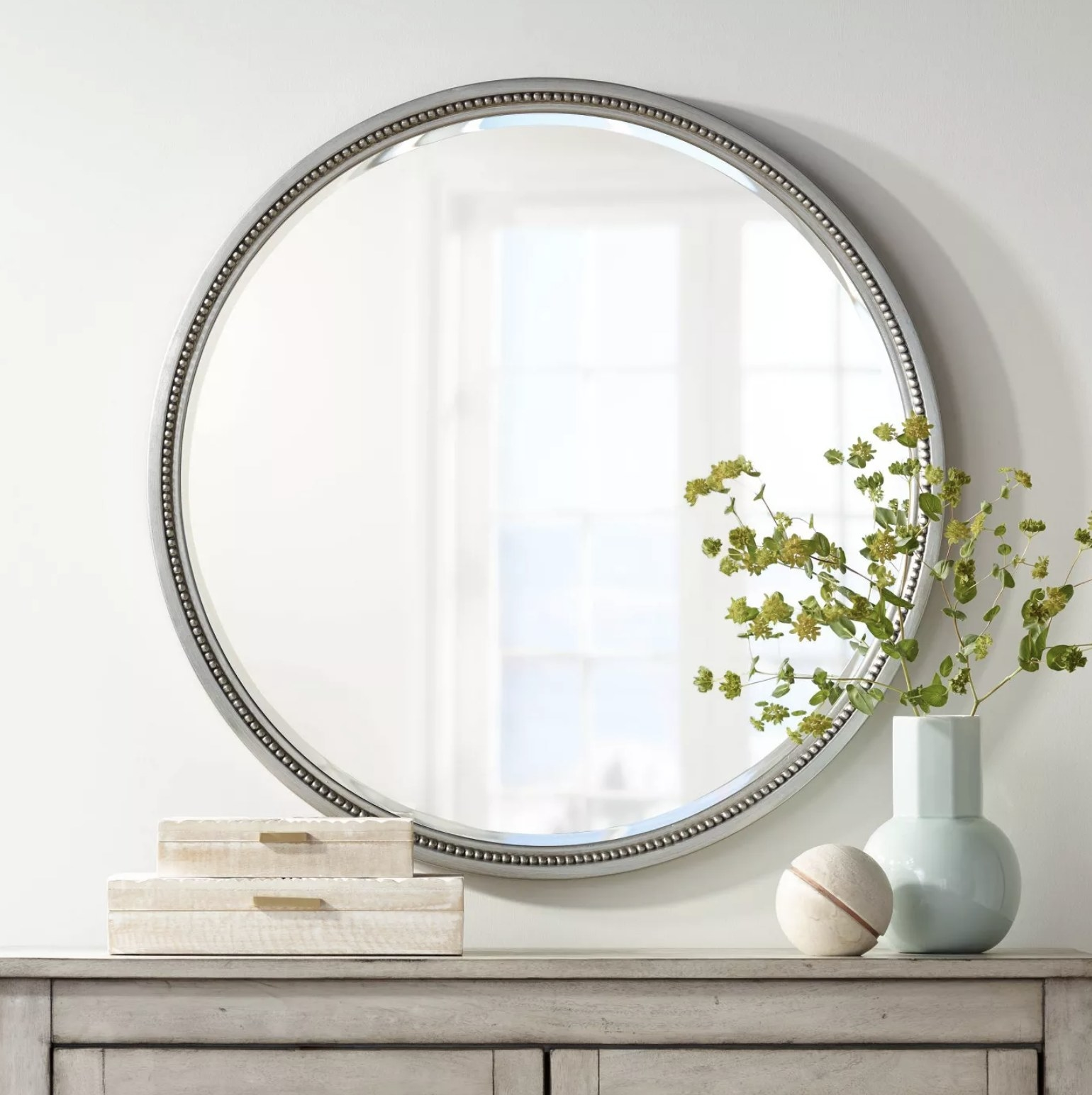 A silver round wall mirror with beaded trim is hung above a console table