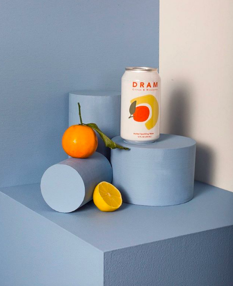 Can of Dram with an orange and lemon