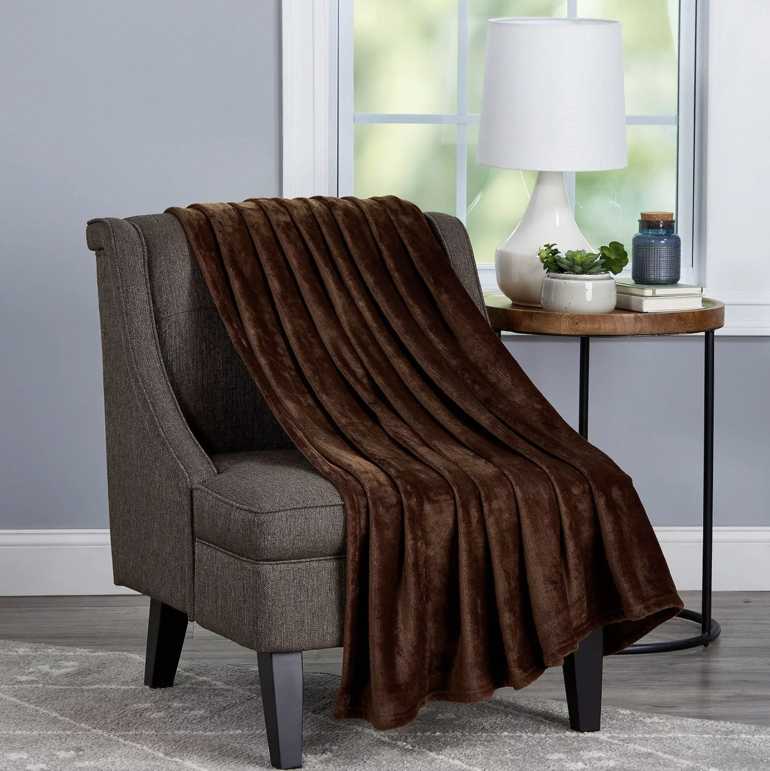 A brown oversized microfiber throw blanket is placed on top of a grey chair
