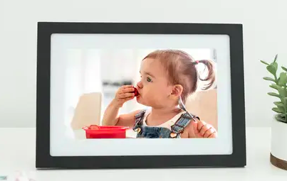 Child eats piece of fruit in photo shown on black-and-white, digital Skylight Frame