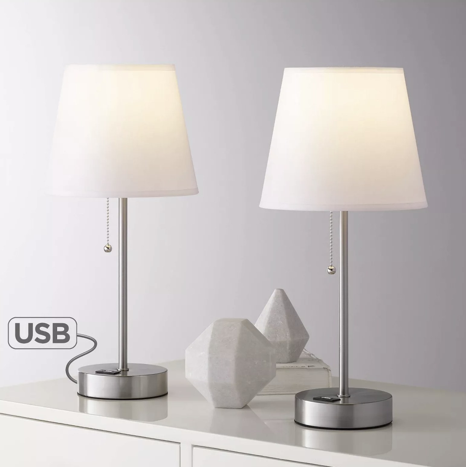 Two stainless steel lamps with usb charging ports on the base sit on a dresser