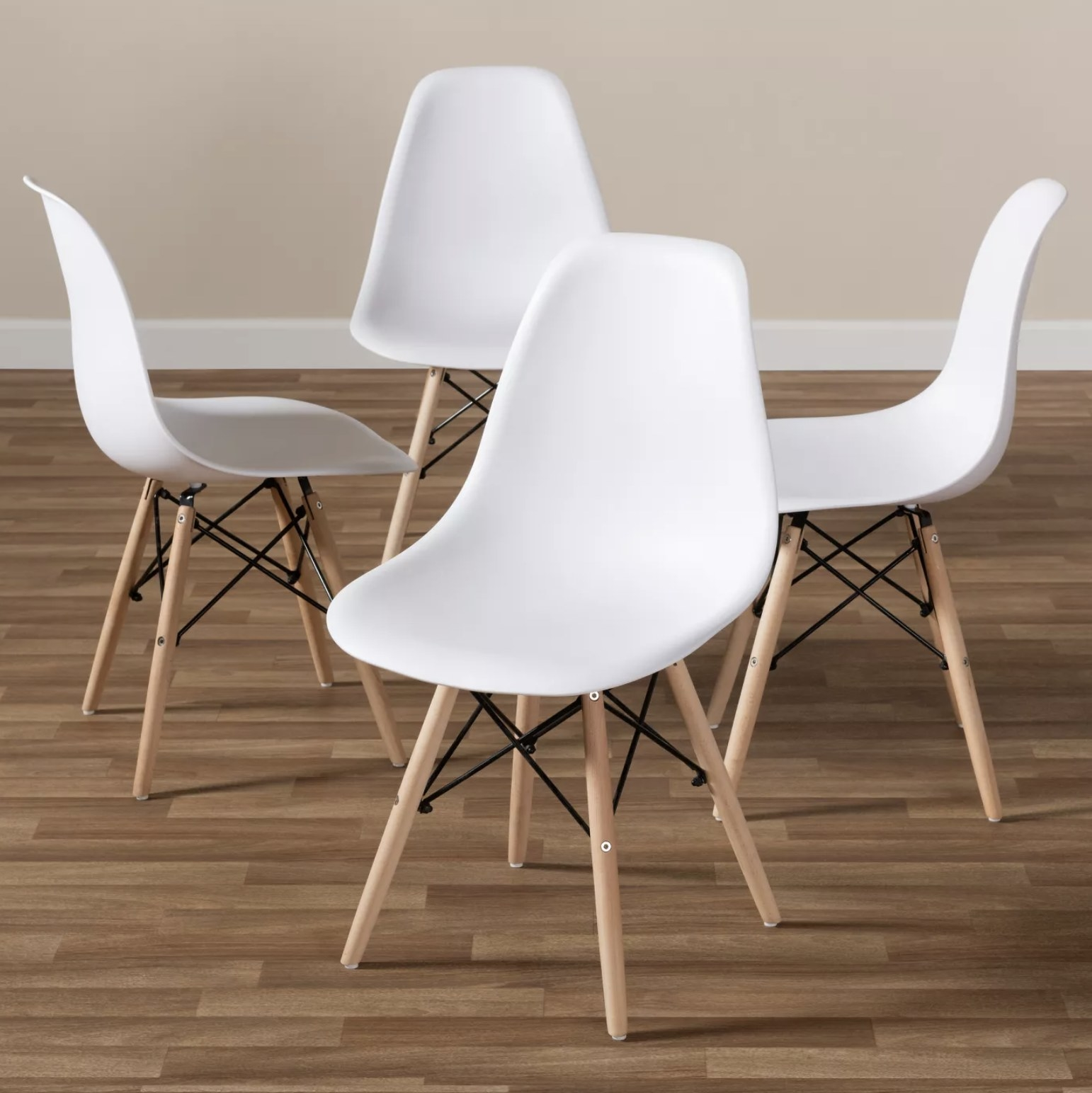 A set of four white mid-century style dining chairs with light wooden legs