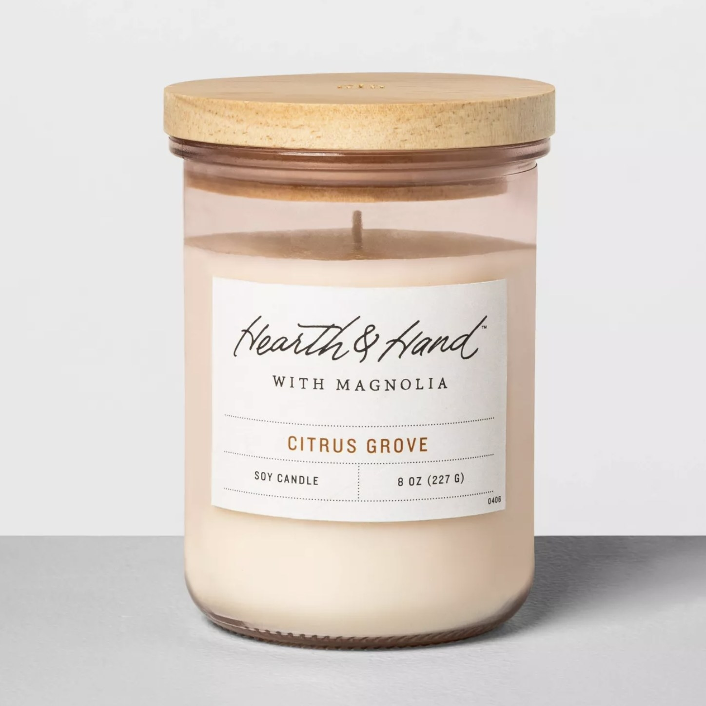 A soy candle in a glass jar with a wood lid in a citrus grove scent