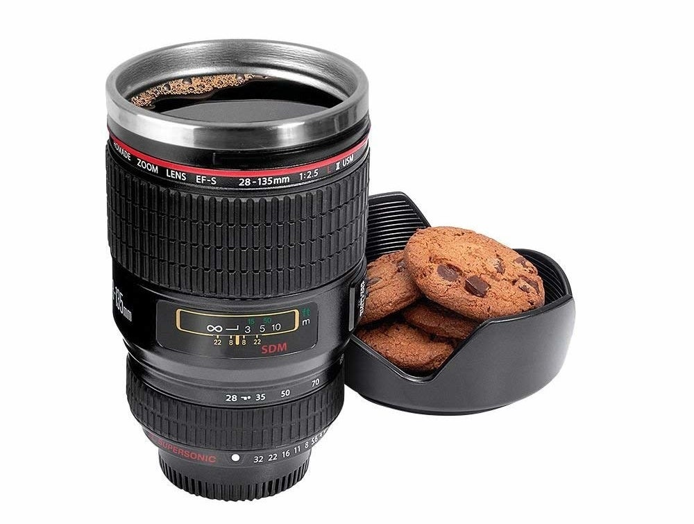 A camera lens shaped mug with a drink in it, and some cookies in the attached cookie holder