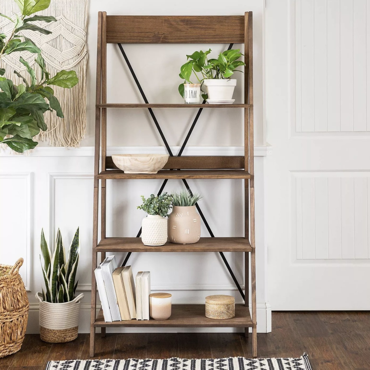 A light wood four-tier ladder bookshelf sits in a living space against the wall with decorative accents on it