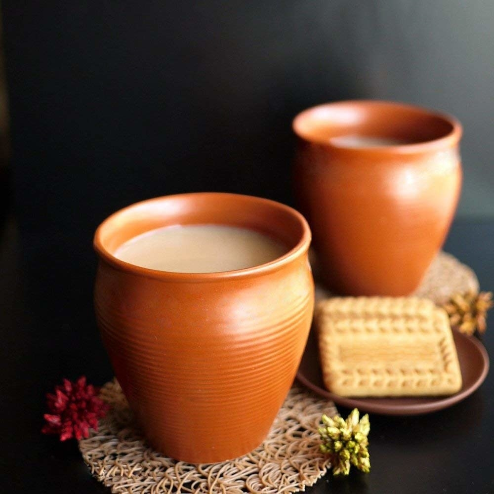 2 clay cups filled with chai and plate of biscuits kept next to them
