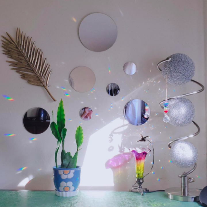 Reviewer shows mirror circle display above their dresser with a tiny plant pot and shimmery disco decoration