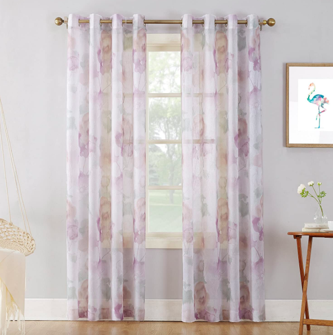 Opaque sheer floral curtains covering a window next to a wooden table and hanging macrame chair