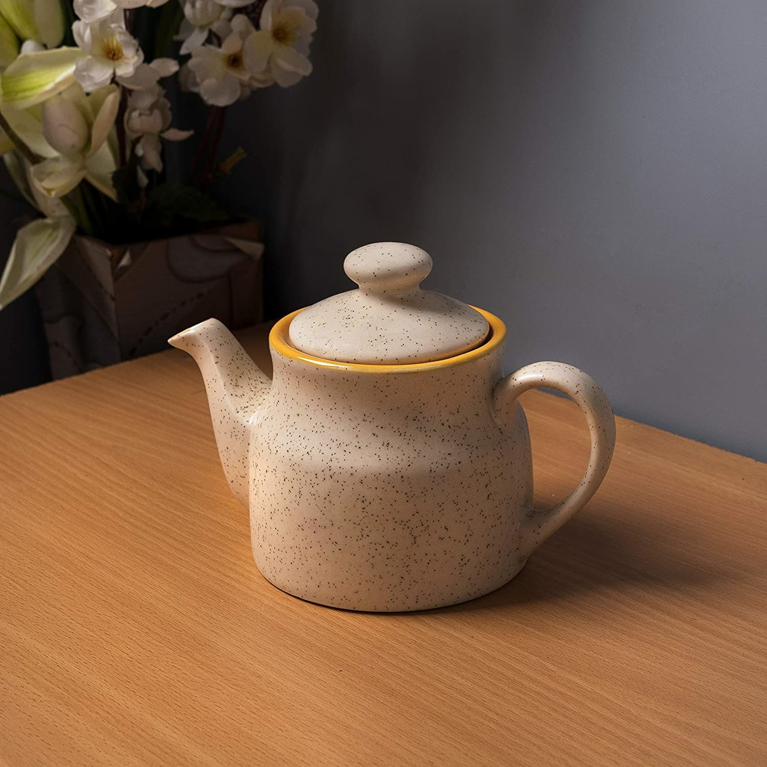A dotted beige ceramic kettle kept on a wooden surface