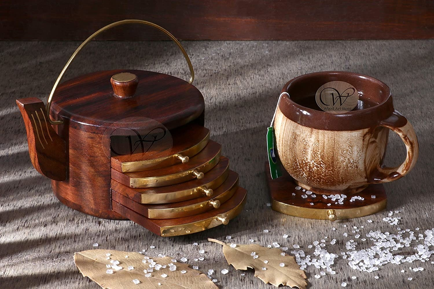 Wooden coasters kept in a kettle-shaped holder and a cup of tea placed on the side.