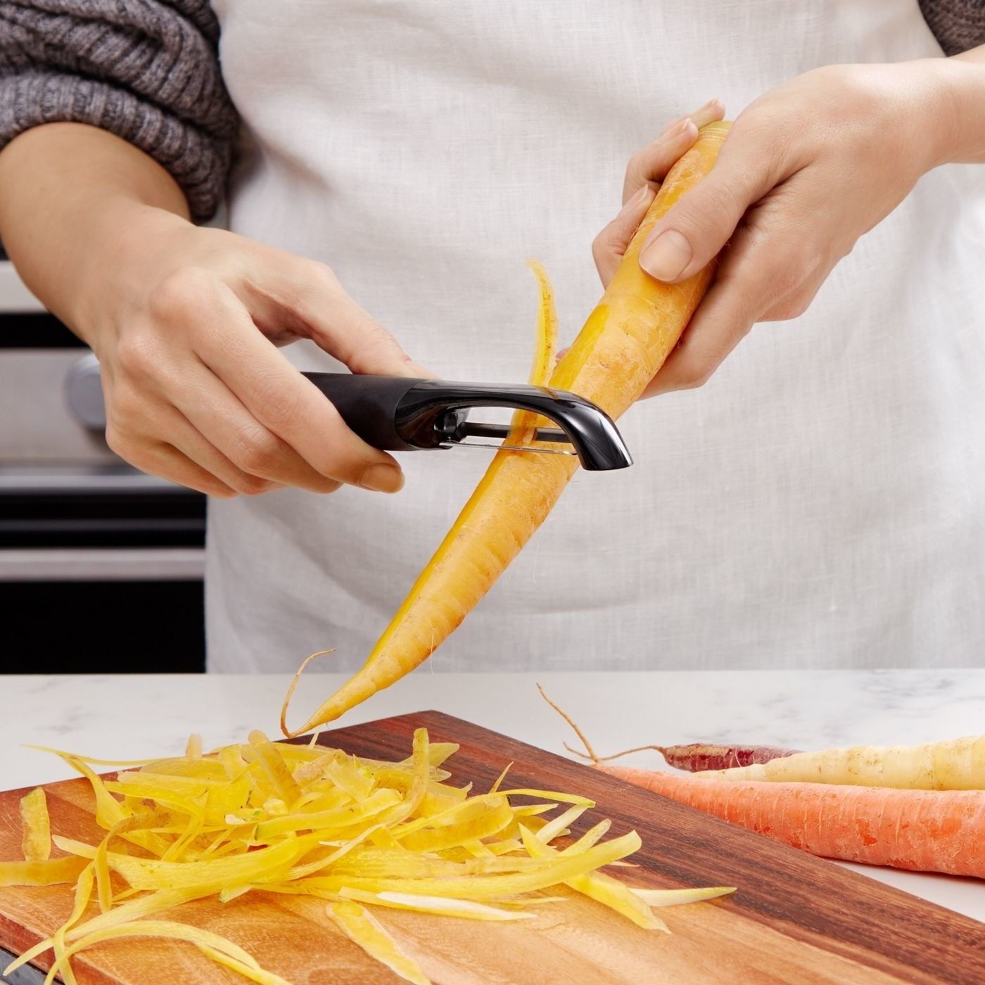 person using a peeler to take the skin off of carrots