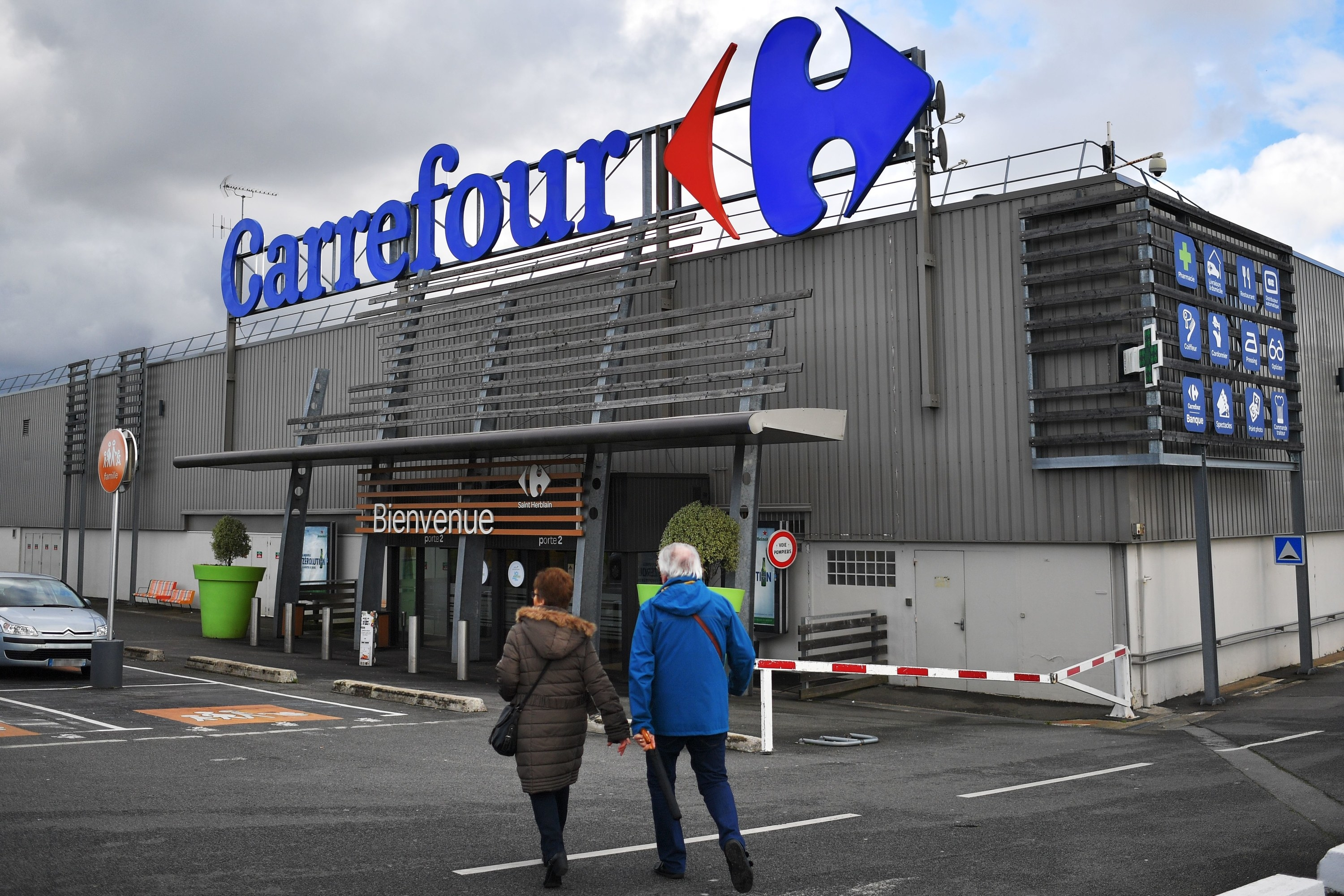 A couple walking into a Carrefour supermarket