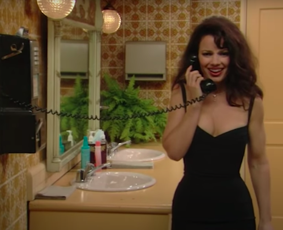 Fran Fine, wearing a fitted black cocktail dress, talking on a payphone in the bathroom.