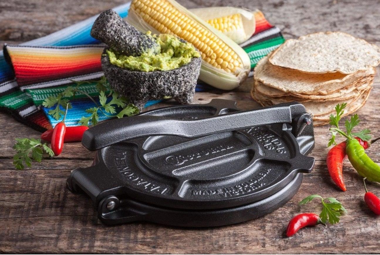 a cast iron tortilla press next to tortillas, guacamole and corn