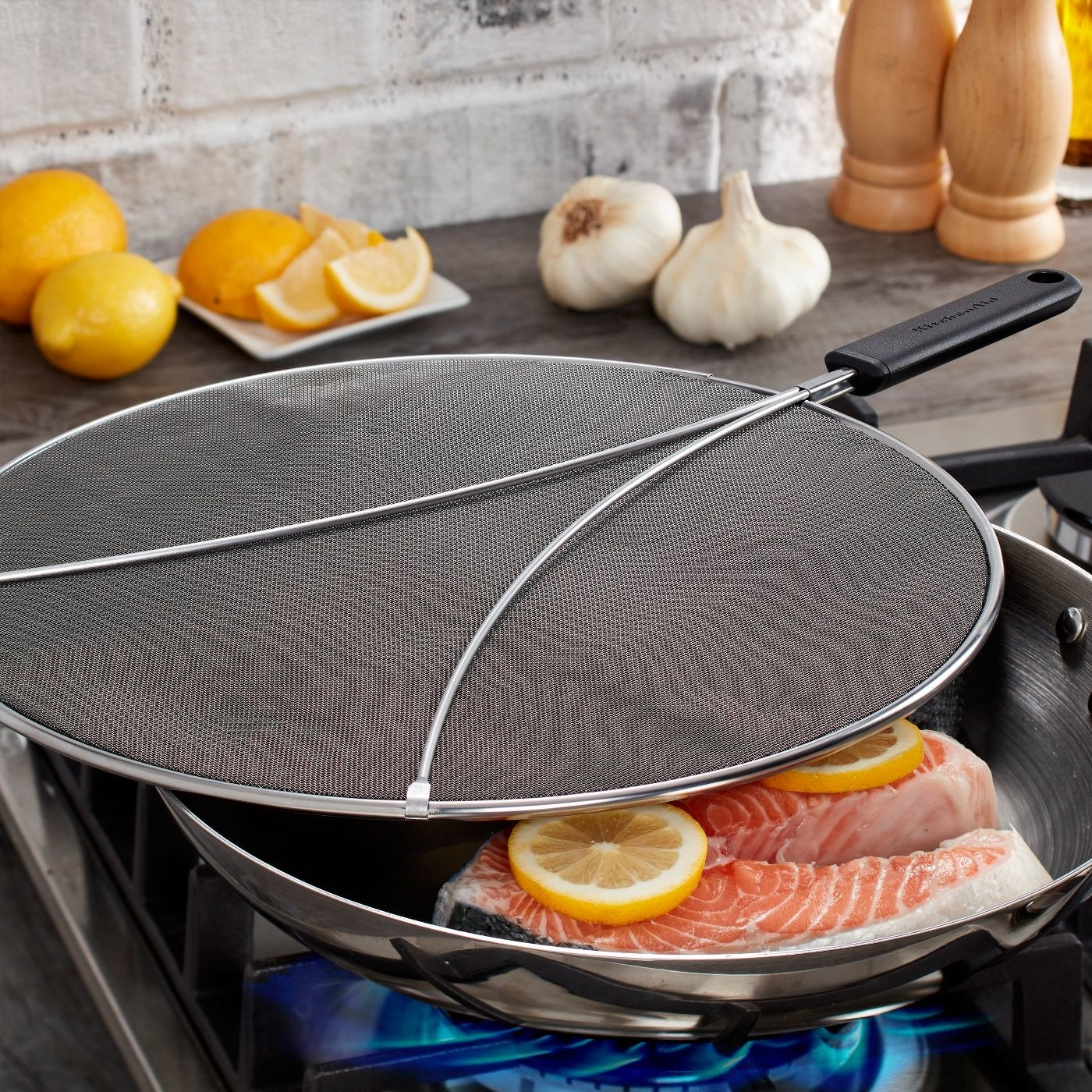 a kitchenaid splatter screen over a pan with salmon