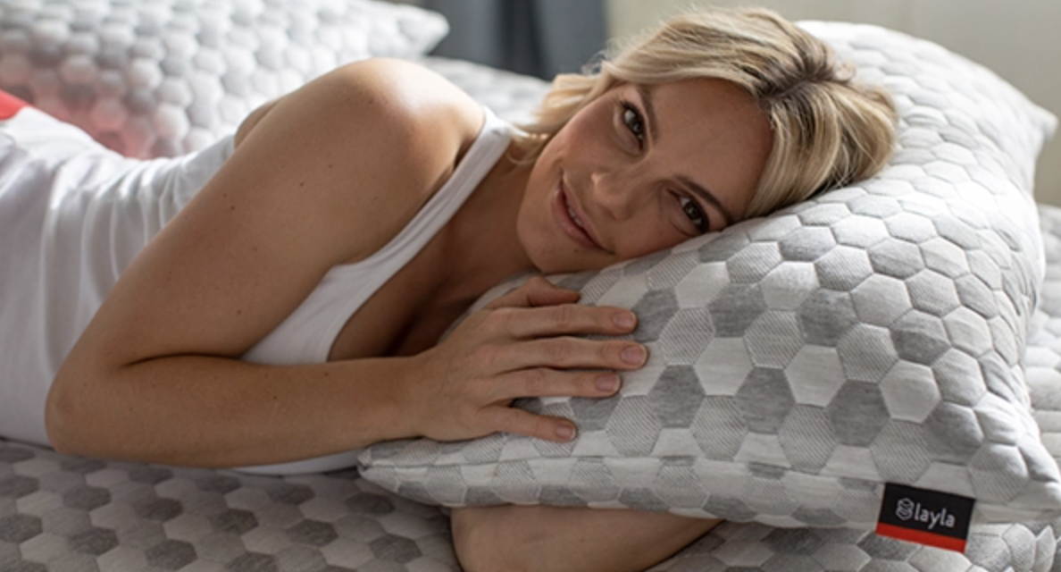 a model laying their head on a grey and white pillow with a hexagon shape on it