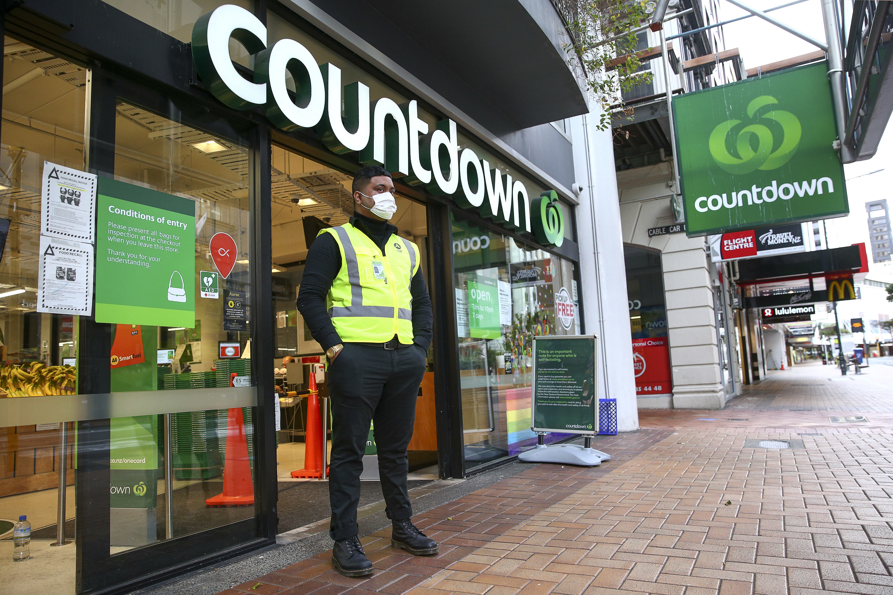 A security guard, in a mask, stands outside a Countdown supermarket