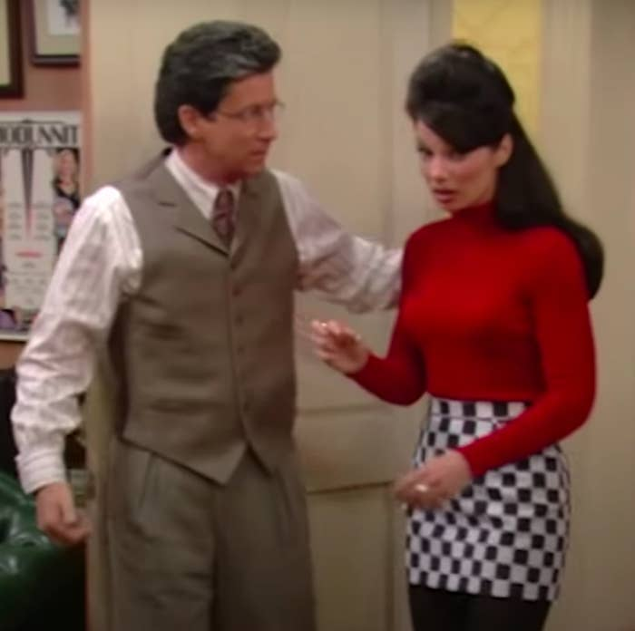 Fran Fine, wearing a black and white checkered mini skirt paired with a red turtleneck, talking to Mr. Sheffield.