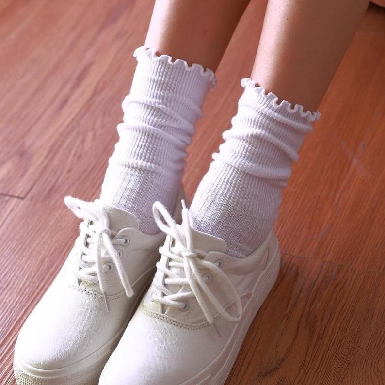 A photo of a kid and her white canvas shoes wearing white ribbed ruffled socks