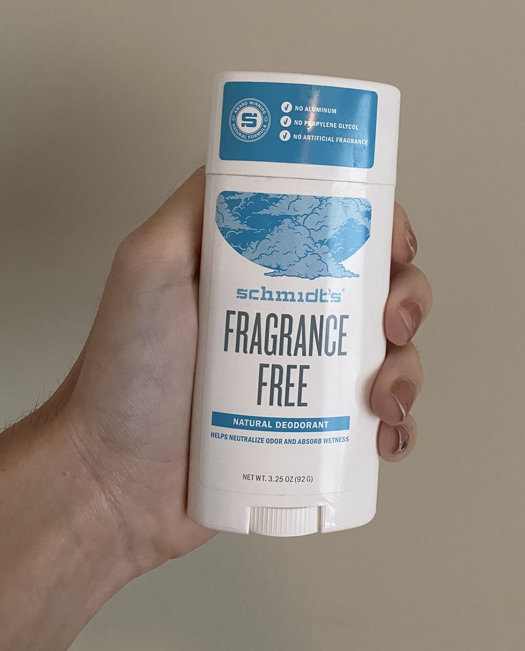 the writer's hand holding the unscented deodorant
