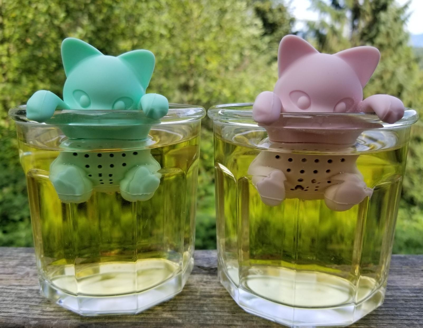 Reviewer pic of teal and pink tea infusers that look like kittens hanging off the inside edge of mugs with yellow tea inside.