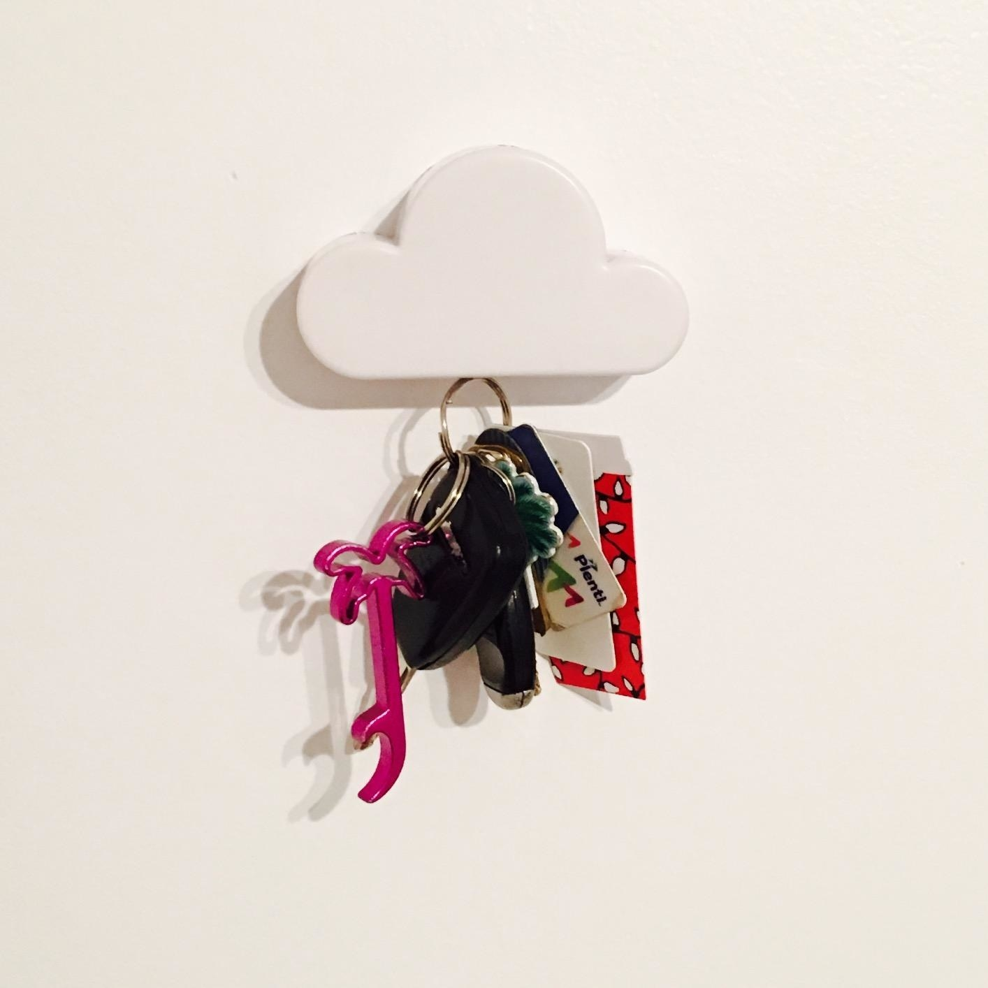 Reviewer pic of the white cloud key holder attached to the wall with a big set of keys hanging from it.