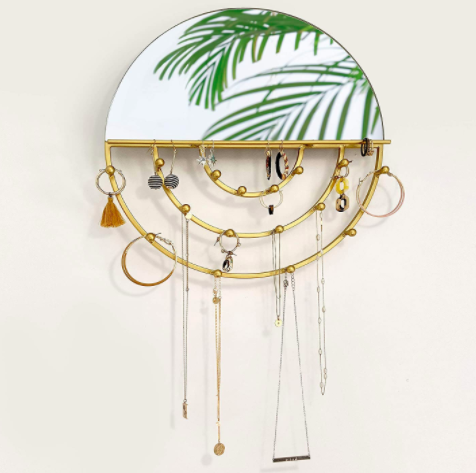 Circular hanging jewelry organizer with necklaces and hoop earrings on a wall