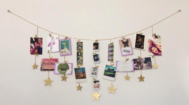 Gold starry photo garland filled with postcards and instant-print pictures hanging on a white wall