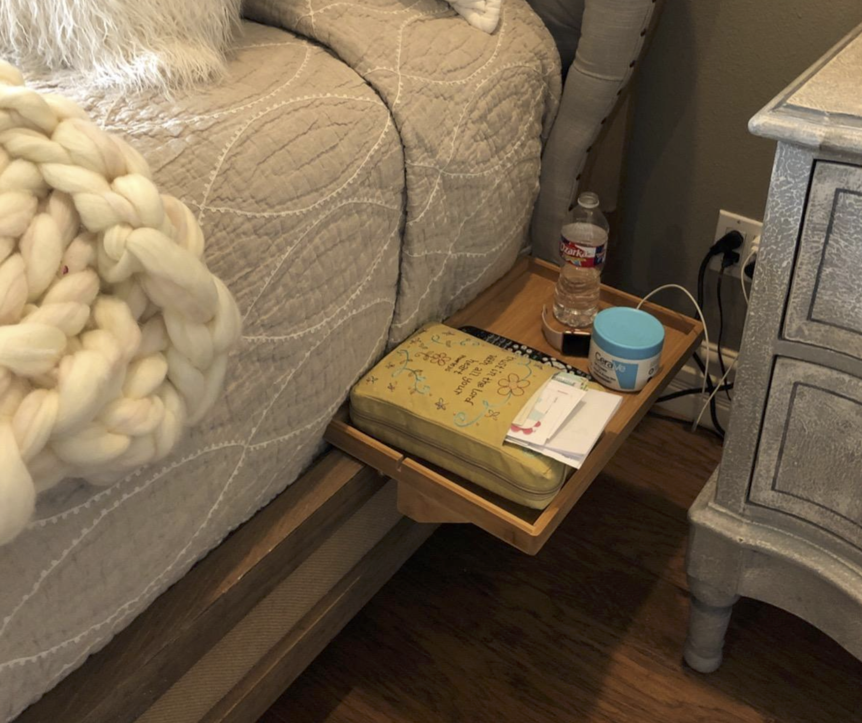 a wooden tray attached to a bed with moisturizer, a bottle of water, a watch, and a book sitting on it