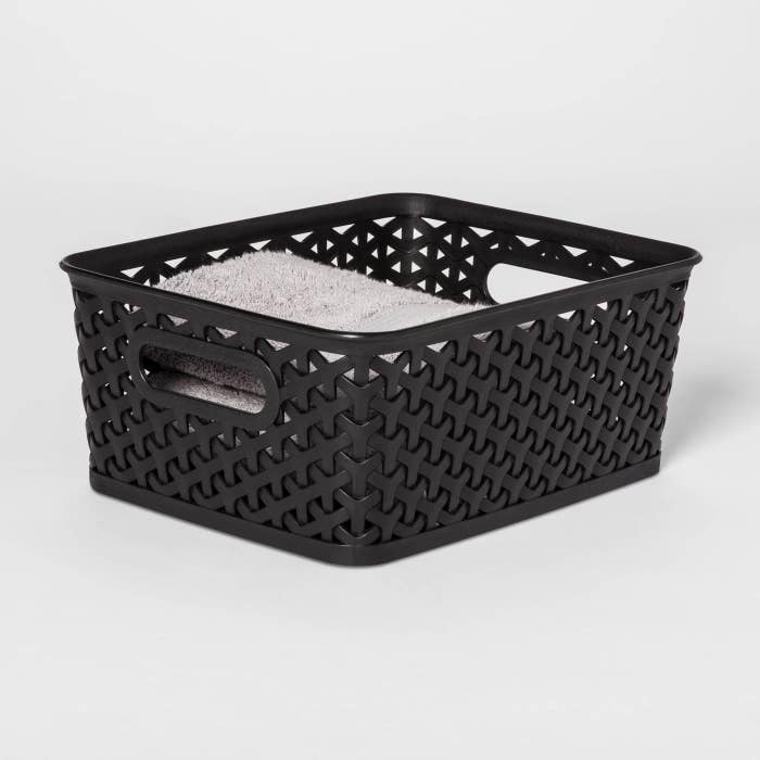 black storage bin with towels inside