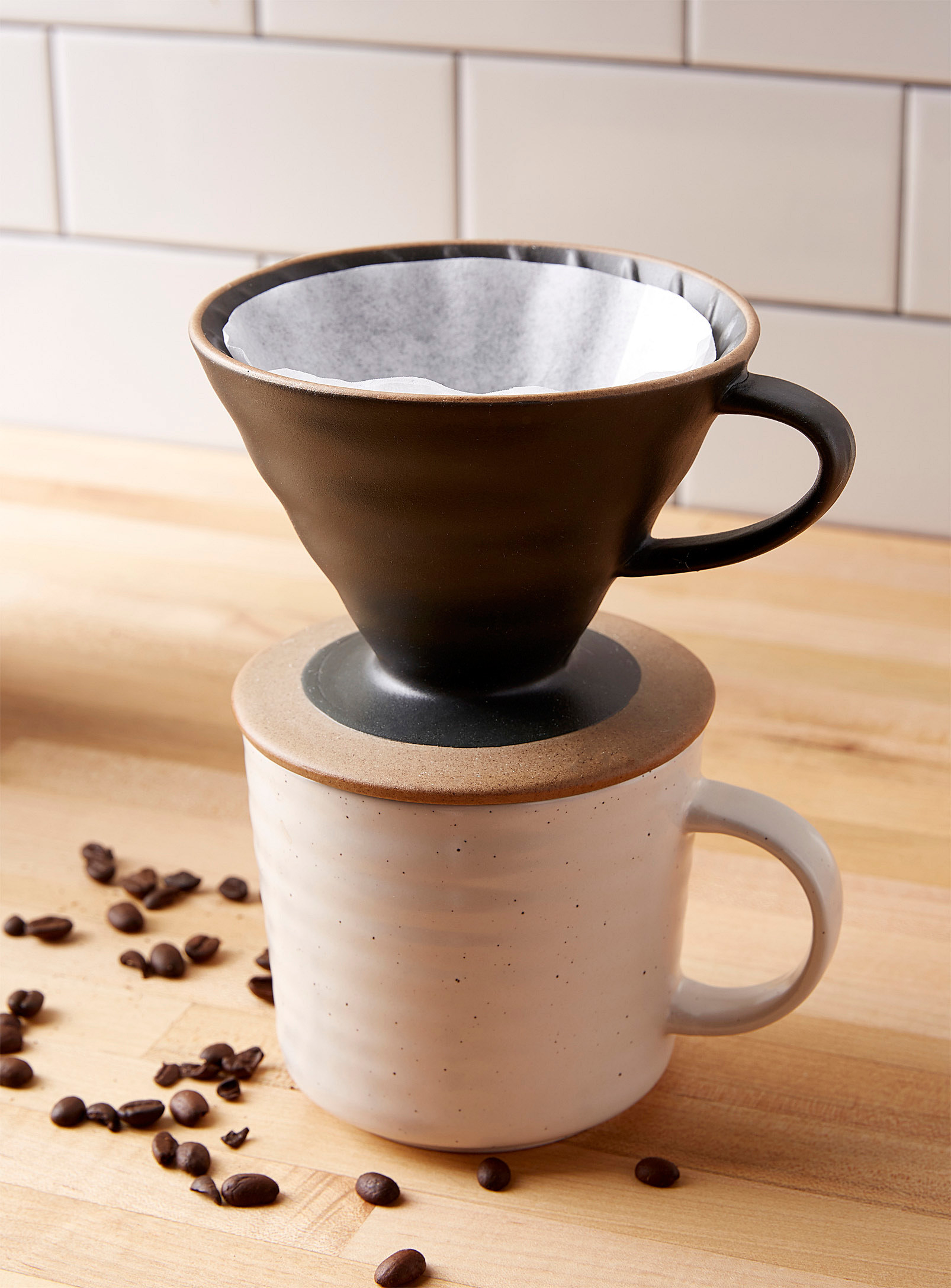 A stoneware pour over coffee dripper with a handle placed on top of a small mug