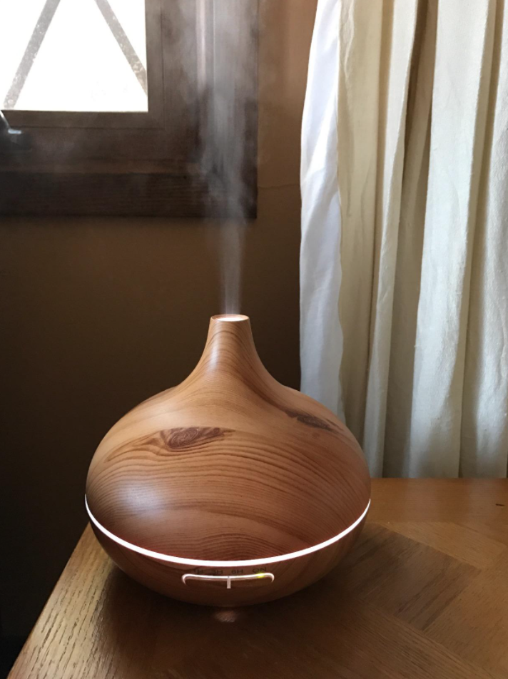 A reviewer's wooden-looking diffuser that's shaped like a gourd with a soft light around the rim