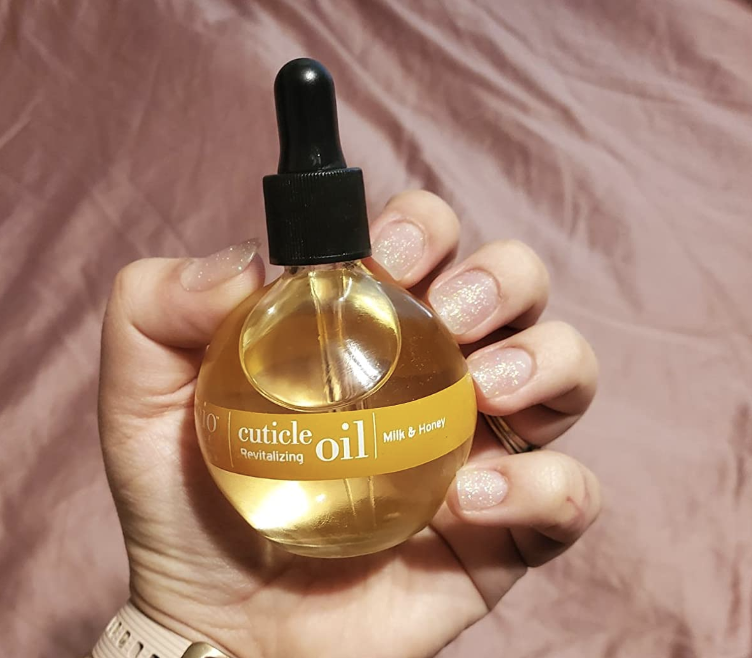 A reviewer holding the bottle, intentionally showing their glittery manicure with healthy looking nails and cuticles